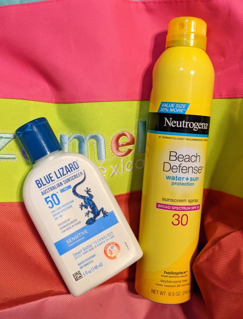 Two bottles of sunscreen on a colorful background