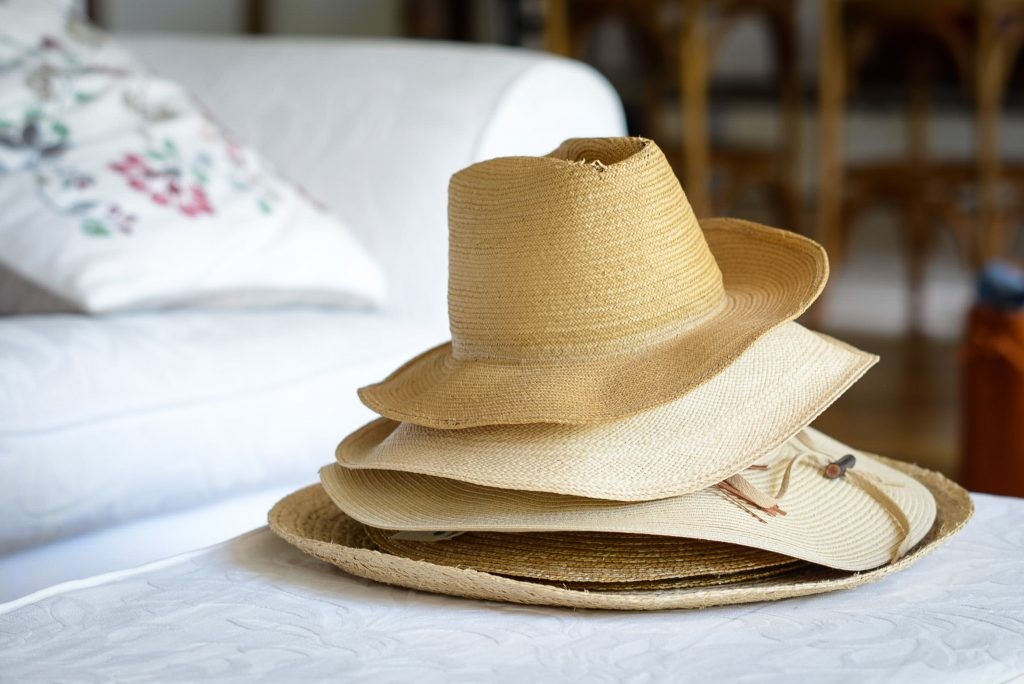 hats stacked together on top of a bed