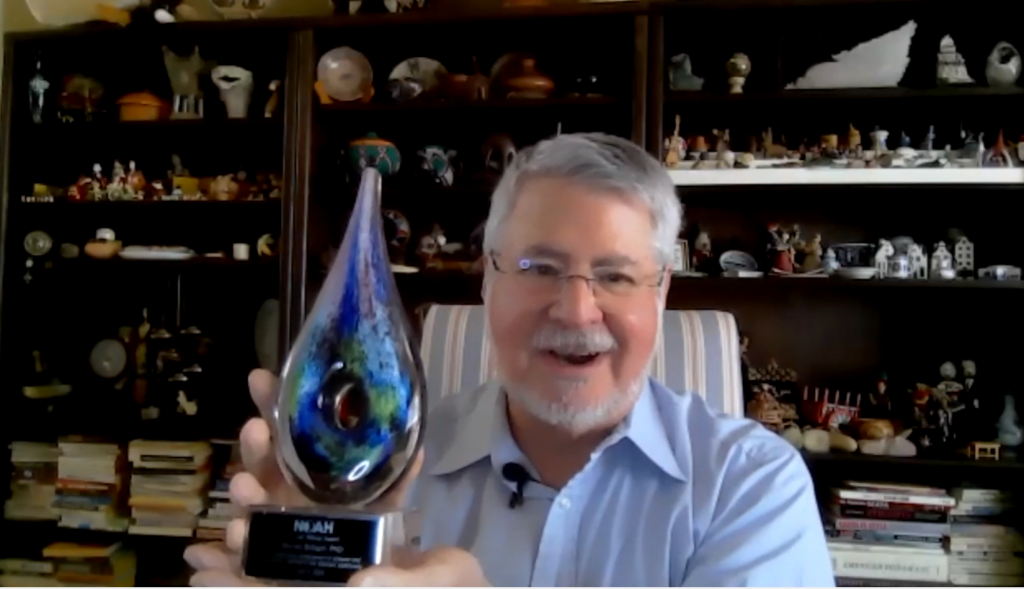 Dr. Murray Brilliant holding an award trophy in the shape of a teardrop with a circle in the center on a square base