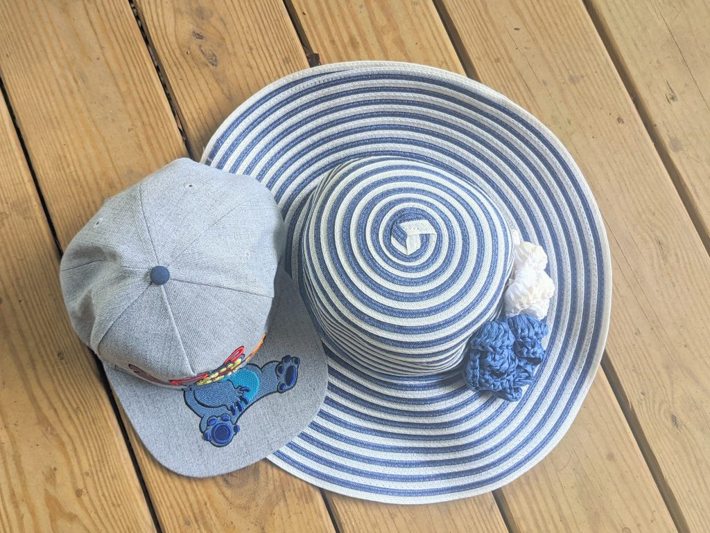 Two hats on a wooden deck, a grey ball cap and a large brim hat with blue and white stripes and flowers.