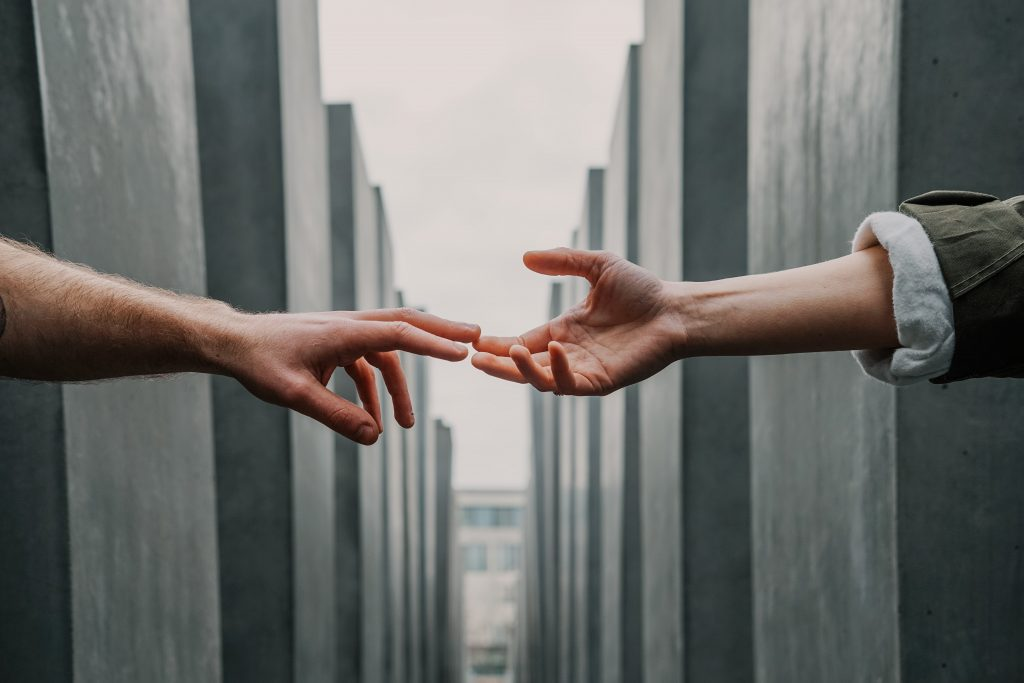 Two hands are reaching out for one another across two columns of metal pillars