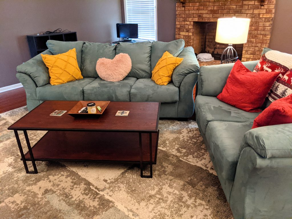 A living room featuring two dusty turquoise couches, various pillows, and a wood and metal coffee table