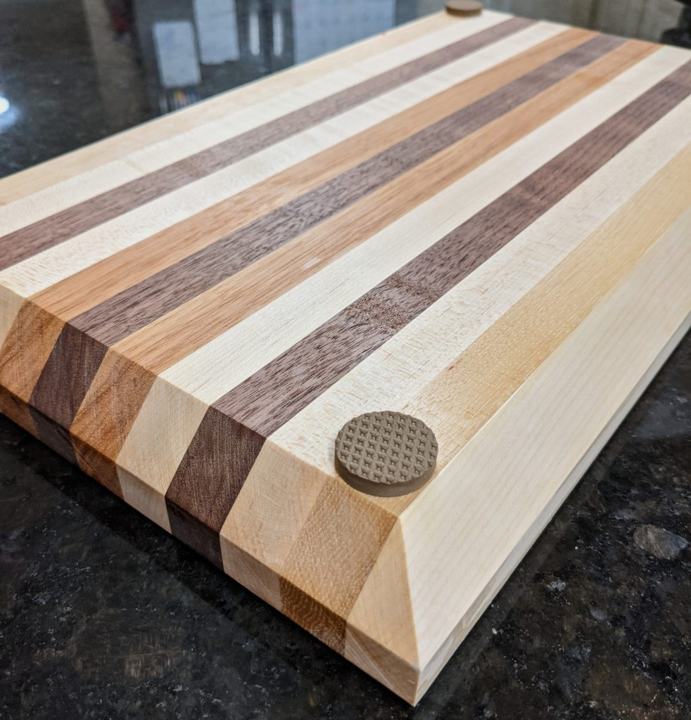 a thick wooden cutting board is upside down showing off the circular non-slip stickers on all four corners