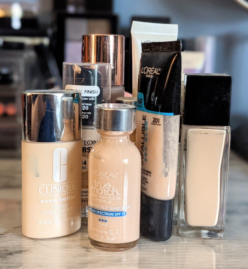 Several bottles of foundation makeup sit on a table